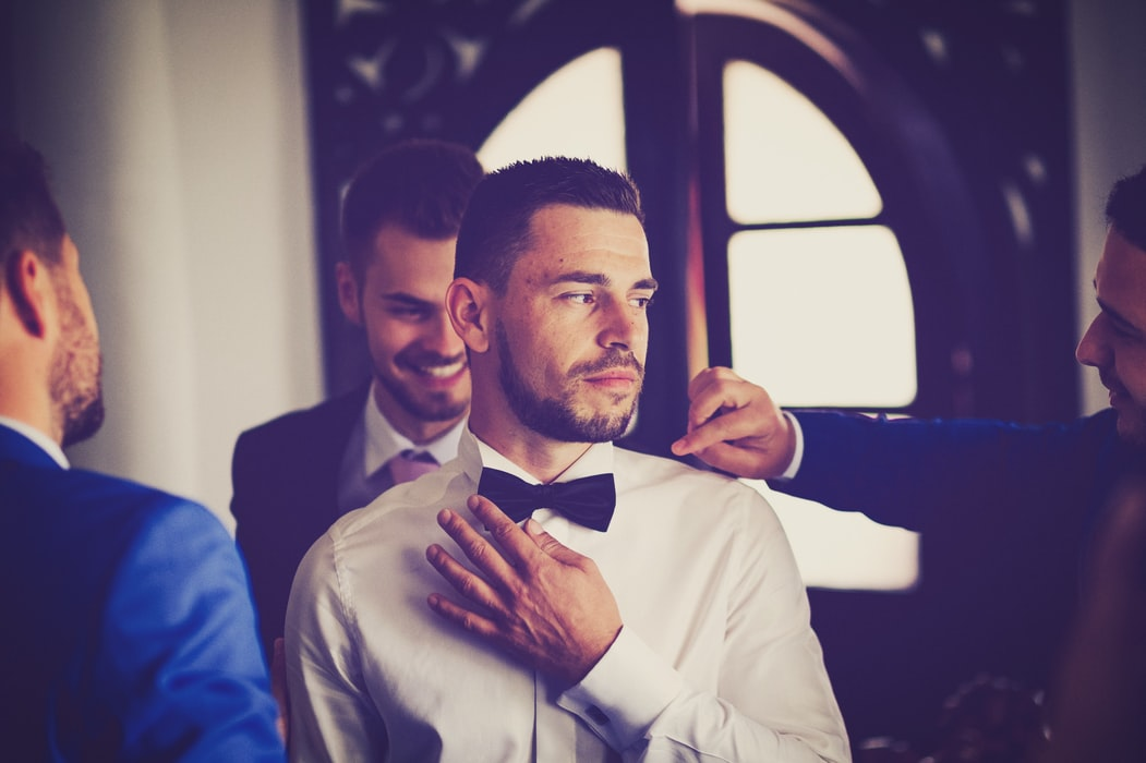 Wedding Day Tips For Groom - Groom Surrounded By Groomsmen