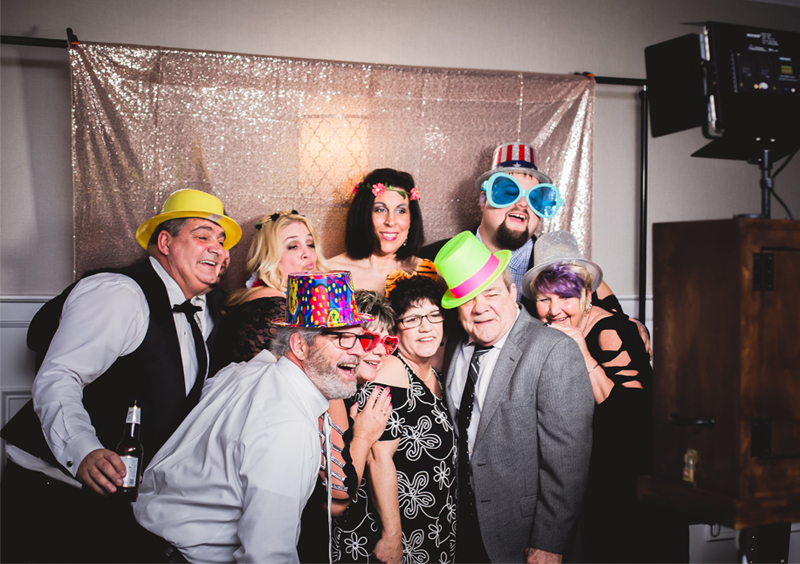 Disappearing Wedding Trends - Group Of People Taking Photo Booth Pictures With Props