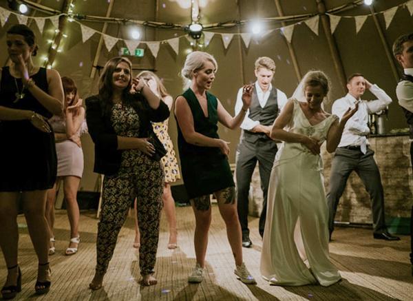 Bride And Guests Dancing AT Wedding Celebration