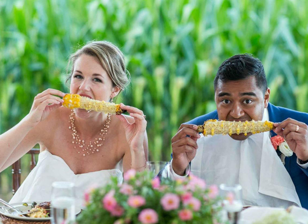 Bride And Groom Eating Corn On The Cob Outside At Wedding Celebration