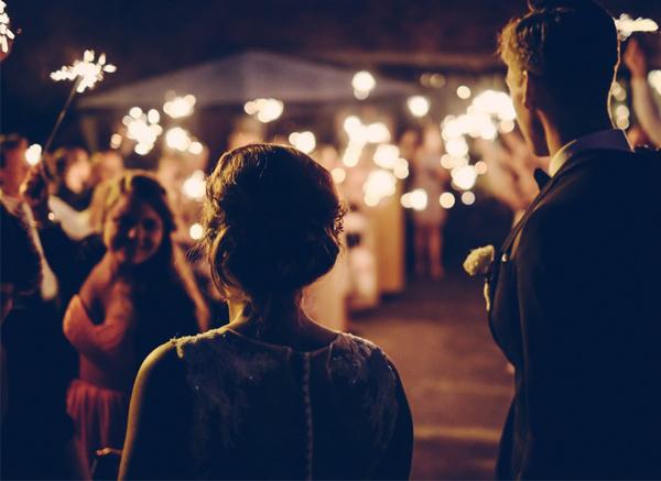 Guests At Wedding Celebration Holding Sparklers Outside