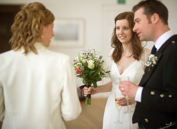 Bride And Groom Talking To A Woman At Their Wedding Celebration