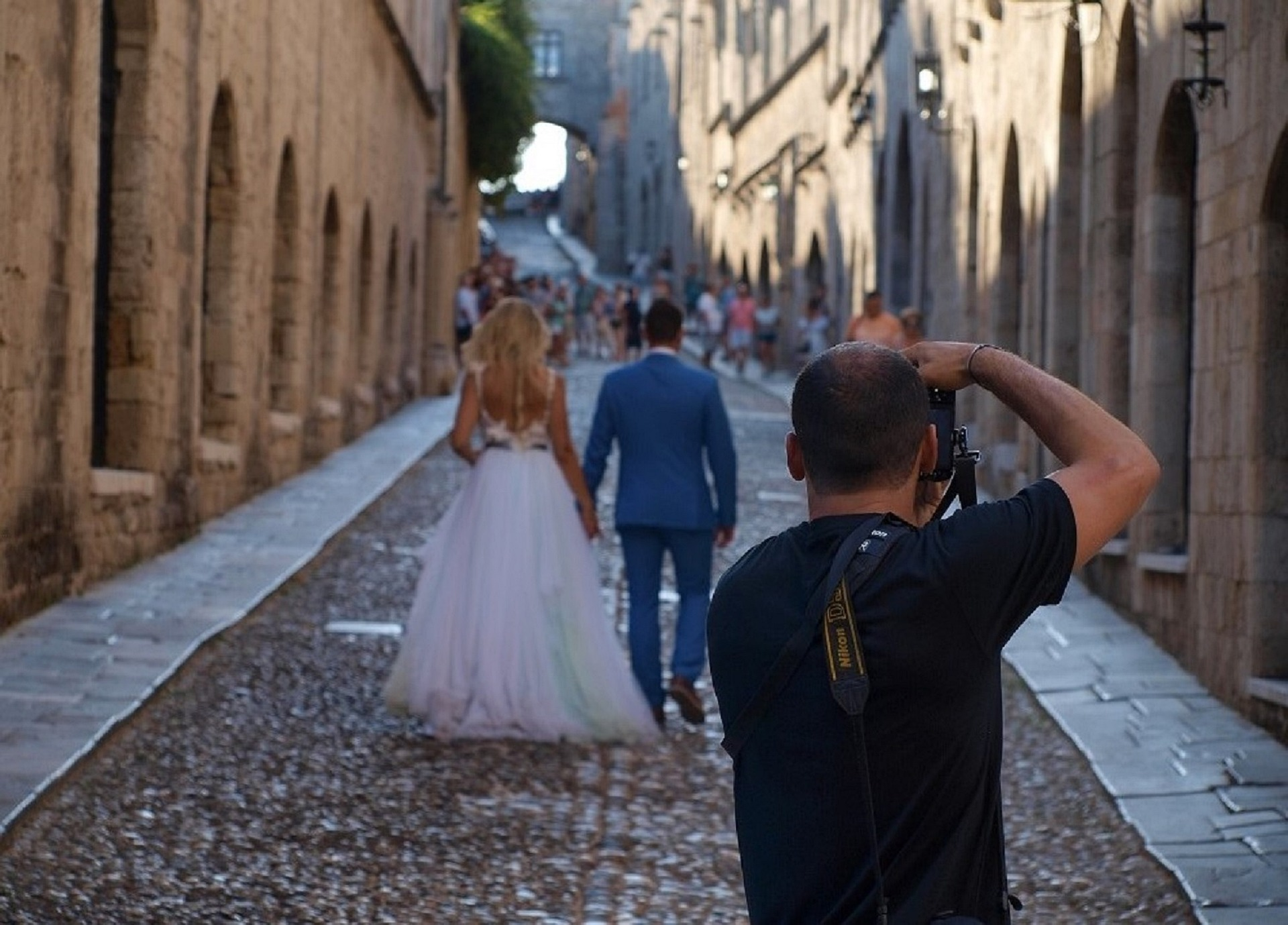 wedding photographer taking photo of bride and groom in small street in europe