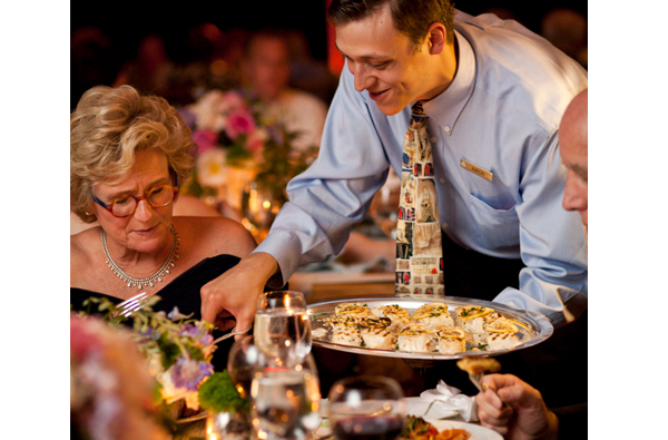 Wedding Reception Food Serving Styles - Family Style - Waiter Serving Woman Food From Platter